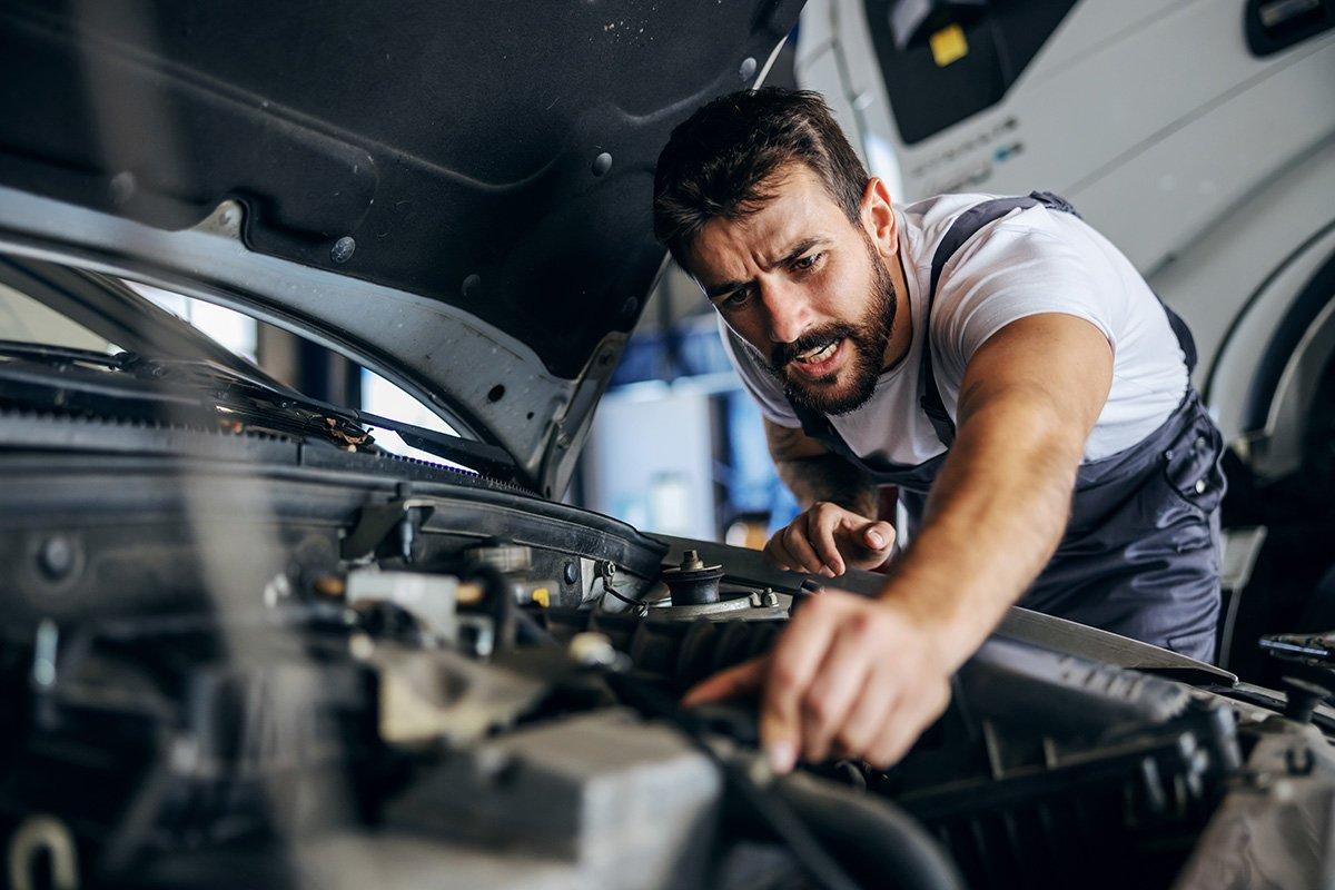 mechanik robi coś przy silniku